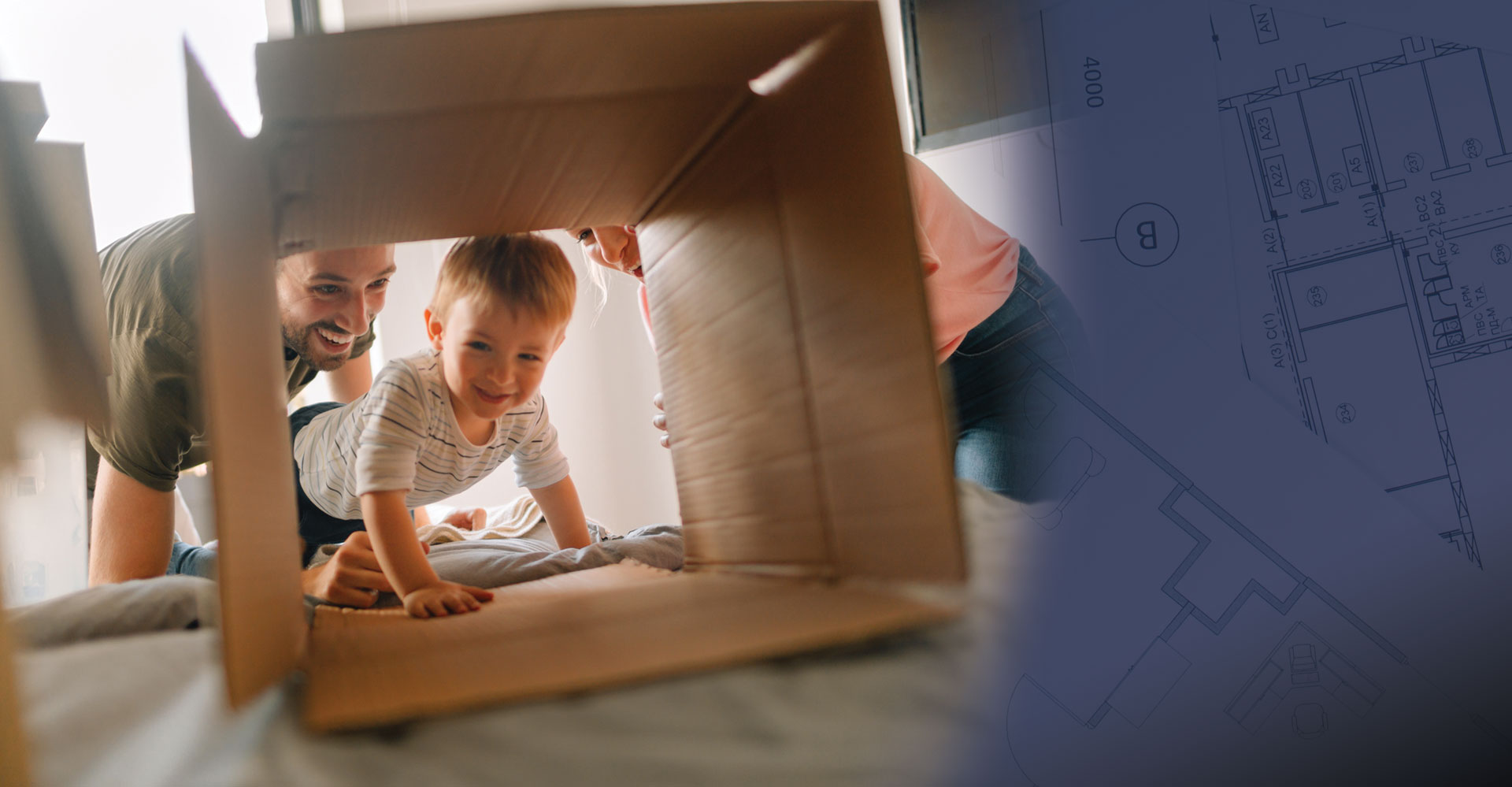 Child crawling through moving box with parent watching